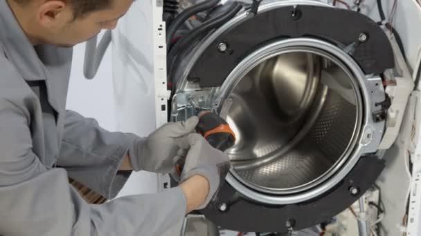 Wartungsmann schraubt Schrauben von der Vorderseite der kaputten Waschmaschine ab.