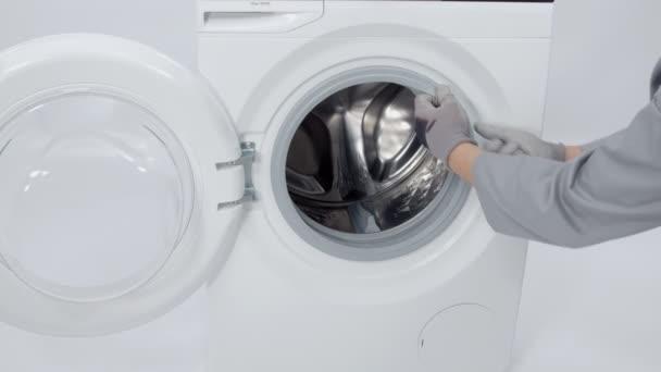 Ein Mann holt eine Waschmaschine hervor. er wird die Waschmaschine reparieren.