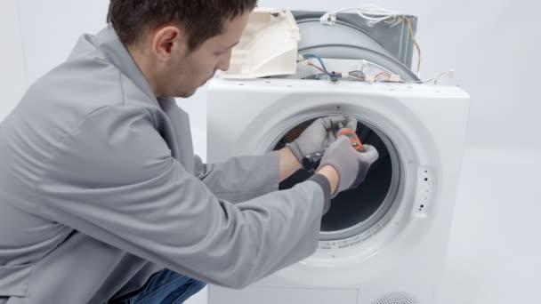 Ein Mann zieht kleine Schrauben heraus und benutzt eine Bohrmaschine. er repariert eine Wasch- und Trockenmaschine.
