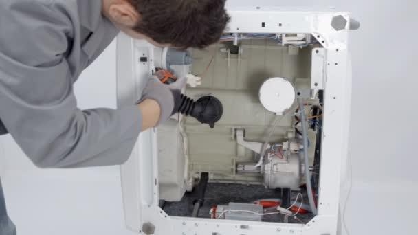 Opravák si bere celý pračku a opravuje ho různými nástroji.