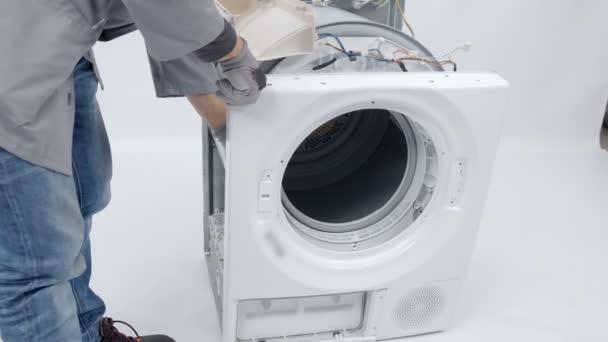 Ein Reparateur repariert die Vorderseite der Waschmaschine. er muss das gesamte Gerät demontieren, um das Problem lösen zu können.