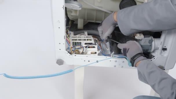 Egy ember rögzítő mosógép csavarhúzóval. Ő használ különböző eszközöket.