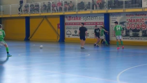 Zelený tým má míč. Teenageři hrají fotbal ve školní tělocvičně a soupeří o cenu. Míč opouští soud.