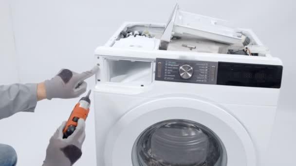 Ein Reparateur demontiert gerade eine Waschmaschine und nimmt Schrauben heraus. er muss das Gerät reparieren.