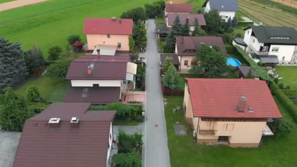 Na konci vesnice můžeme vidět pár domů. Příroda je krásná a zelená. Je letní čas. Letecký snímek.