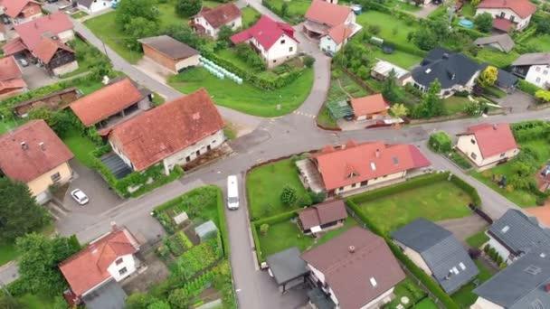 Látunk egy fehér furgont, ami hátrafelé megy. Légi felvétel. Gyönyörűen zöld a környék..