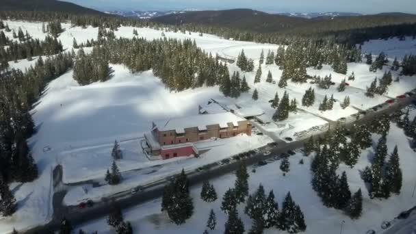Auta projíždějí kolem velké restaurace a hotelu ve vesnici v lyžařském středisku. Letecký snímek.