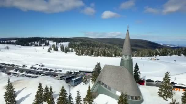 Můžeme vidět malý kostel v lyžařském středisku. Většinu krajiny pokrývá sníh. Je krásný zimní den..