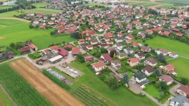 Krásná a klidná vesnice uprostřed Slovinska. Letecký záběr. Domy mají červené střechy. Je léto..