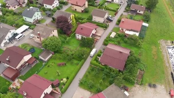 Bílá dodávka projíždí vesnicí. Letecký záběr. Je léto a všechno je zelené..