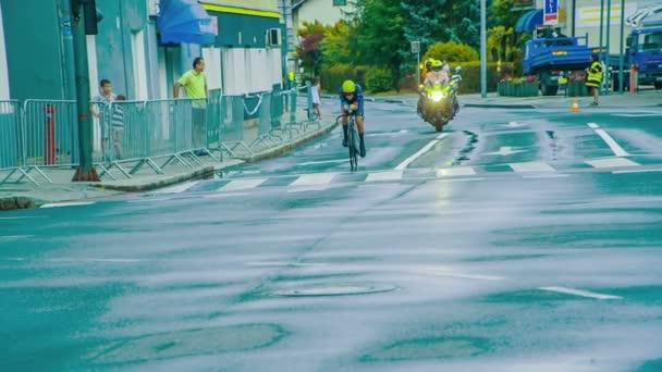 Zwei Motorradfahrer fahren auf glatter Straße hinter einem Rennradrennfahrer.