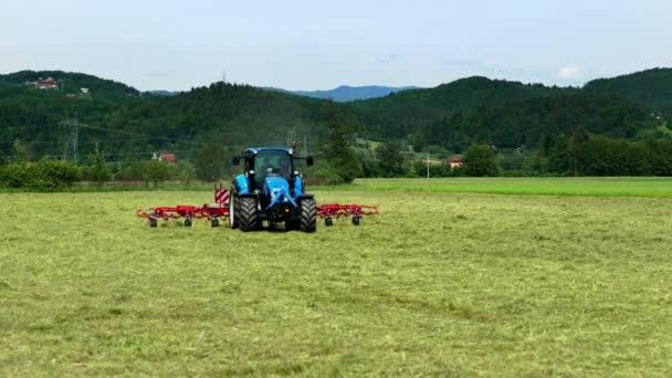 Farmář sedící v traktoru tvrdě pracuje a v létě připravuje seno. Rotační hrábě se pohybují rychle.