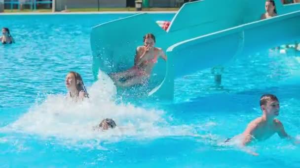 DOMZÁLIA, SZLOVÉNIA - 20. Június 2015 Fiatal tizenévesek szórakoznak, hogy vízicsúszda. Nevetnek és jól érzik magukat a barátaikkal..