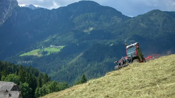 A tractor is preparing hay on a steep hill. There are beautiful mountains in the background and the view is amazing.