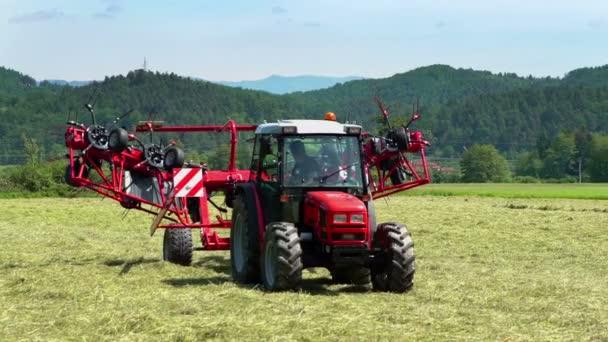 A gép lassan összecsukódik, amikor egy farmer megnyom egy gombot egy traktorban..
