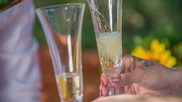 Langsam gießt ein junger Mann noch etwas Champagner in zwei separate Gläser. Ein Paar hat ein Date im Freien.