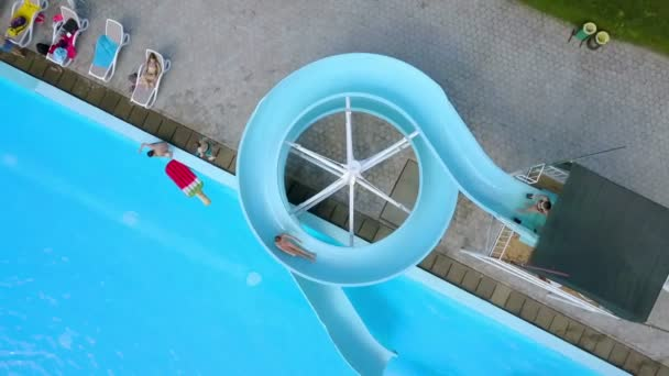 DOMZALE, SLOVENIA - 20. JUNE 2015  A girl is travelling down a water slide and then she falls into a swimming pool. Aerial shot.