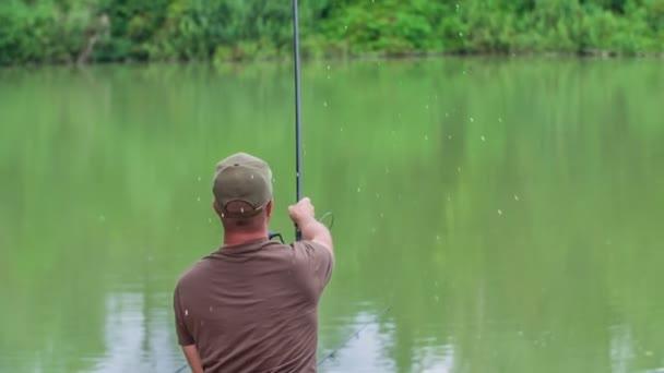 Egy fiatal halász elegánsan bedobja a horgászbotot a vízbe, és egy egész délutánt fog horgászni..