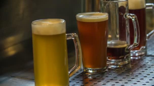 DOMZÁLIA, SZLOVÉNIA - 16. JÚLIUS 2018 Néhány kancsó söröző áll a pulton a bárban. A szurkolók isznak, amikor kosárlabdát néznek..