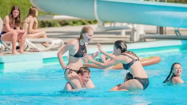 DOMZÁLIA, SZLOVÉNIA - 20. Június 2015 Két lány ül a barátai vállán, és birkóznak. Próbálják megtartani az egyensúlyt, és nem beleesni a vízbe..