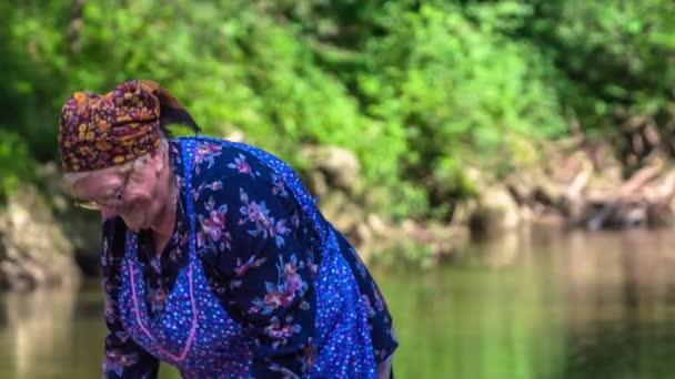 Eine alte Dame ist glücklich und lächelt, wenn sie im Wasser arbeitet und Wäsche wäscht. Sie ist in altmodischer Kleidung gekleidet.
