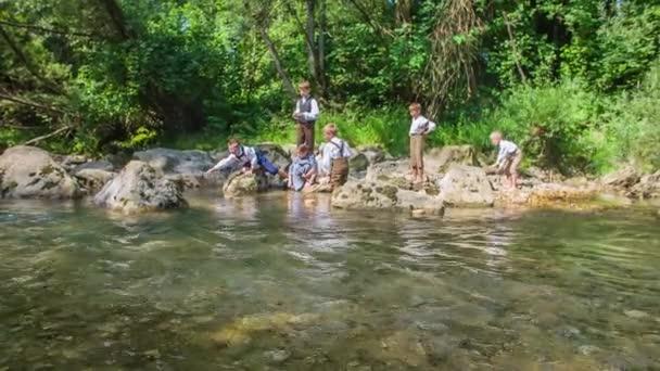 Děti tráví svůj čas u řeky, hrají si s vodou a pozorují přírodu.