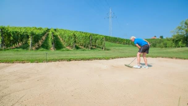 Tahle žena hraje golf. Ona je také pomocí hrábě, aby se písek ještě předtím, než začne hrát další kolo.