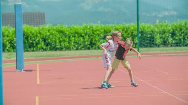 GRIZE, SZLOVÉNIA - 10. Június 2017 Két fiú boldog és birkóznak egy kicsit. A gyerekeknek remek napjuk van odakint, és a sportlétesítményben játszanak. Nyár van..
