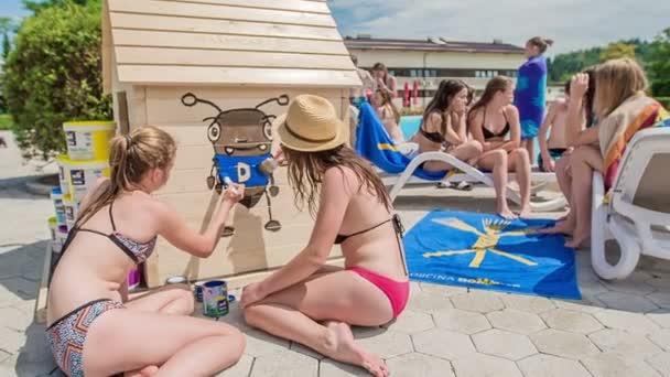 DOMZÁLIA, SZLOVÉNIA - 20. Június 2015 Két lány egy kék színű szöcske testét festi. Nagyon kreatívak..
