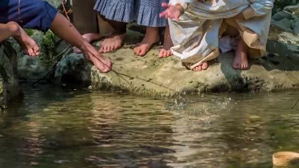 Junge Mädchen stehen am Ufer eines Flusses und spritzen mit Wasser herum. Es ist ein schöner und sonniger Tag.