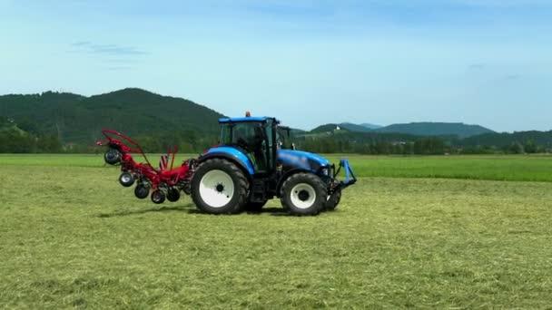 Řídí se modrý traktor a stroje se pomalu skládají. Je krásný letní den..