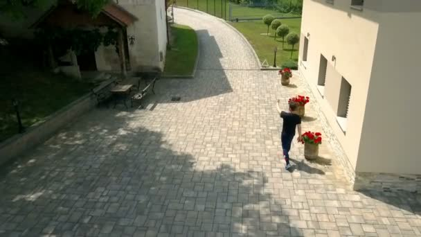 A man walks past a big house and he signals to the children to come closer and they start running towards him.