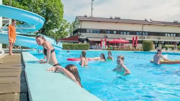DOMZÁLIA, SZLOVÉNIA - 20. Június 2015 Két lány kiszáll a medencéből. Meleg nyári nap van..