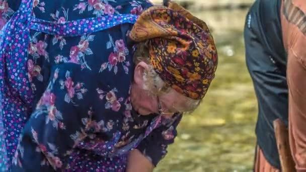 Schwer erwerbstätige ältere Frauen waschen in einem Fluss Wäsche. So haben sie es damals gemacht.