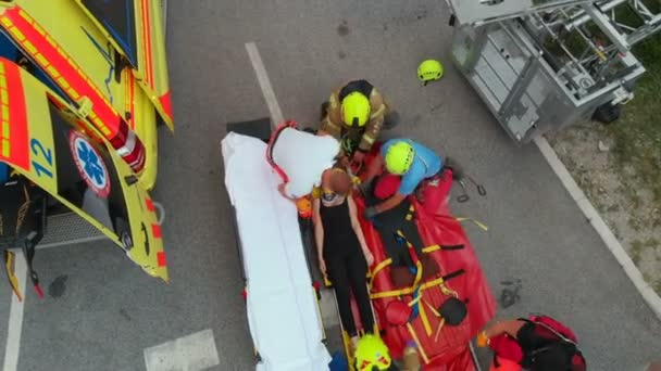 A climber hurt her neck when climbing up on the wall of a building. Rescuers are putting her into an ambulance and will take her to the hospital. She got injured.