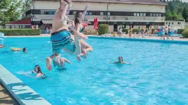 DOMZÁLIA, SZLOVÉNIA - 20. Június 2015 Három tanuló ugrik a vízbe egyszerre. Nyár van és süt a nap. Jól érzik magukat..