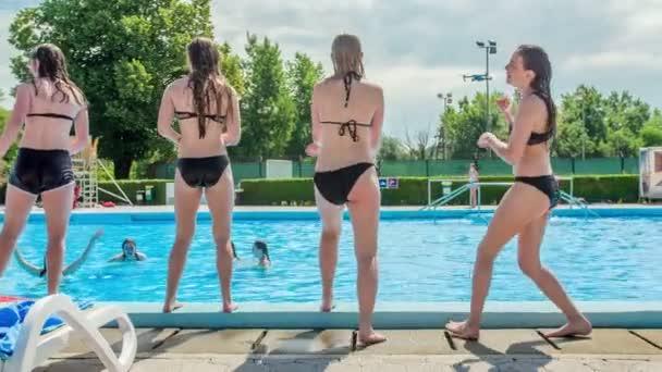 DOMZÁLIA, SZLOVÉNIA - 20. Június 2015 A fiatal lányok jól érzik magukat, és a medencén kívül táncolnak. Itt a nyár és a szórakozás ideje..