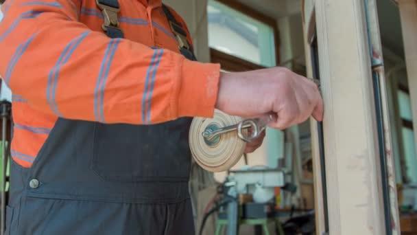 Truhlář používá malý a velký klíč, aby upravil zrcátko na veteránském autě, které vyrábí doma ve své dílně..