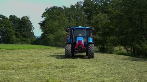 Na velké travnaté ploše se blíží velký modrý traktor. Je k němu připojen rotační stroj na hrábě.
