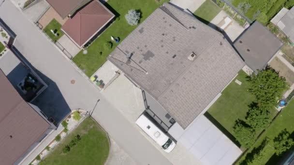 Všechny domy v této čtvrti mají tmavé střechy. Ulice vypadá zelené, klidné a klidné.