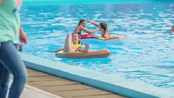 DOMZÁLIA, SZLOVÉNIA - 20. Június 2015 Három lány hűvös felfújható levegő szőnyegen. Élvezik az időt a medencében, és csak pihennek..