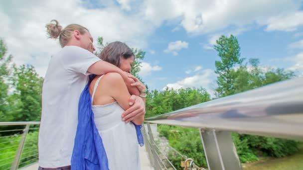 Egy férfi ölelgeti a nőjét, és egy hídon állnak és szerelmesek..