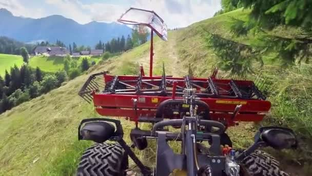 A tractor is moving uphill on a grass and is approaching the concrete road. The scenery is amazing - everything is green and blue and beautiful.