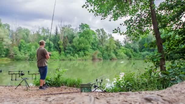 Egy halász várja, hogy kifogja a halat. A tó mellett áll és horgászik..