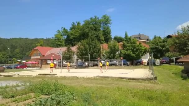Z volejbalového hřiště se valí míč na zelené trávě. Je slunečný letní den.