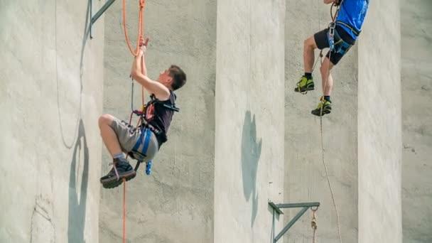 Két hegymászó mászik felfelé az épületen. Egyikük elkezd lenézni..