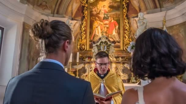 DOMZALE, SLOVENIA - 19. JULY 2018  Bride and groom are at the altar and they are listening to the priest who is reading the words from the Bible.