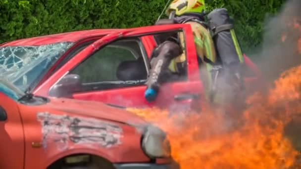 DOMZALE, SLOVINSKO -7. 2018 Hasič vynáší oběť z auta, když je na autě požár. Tým hasičů má trénink..