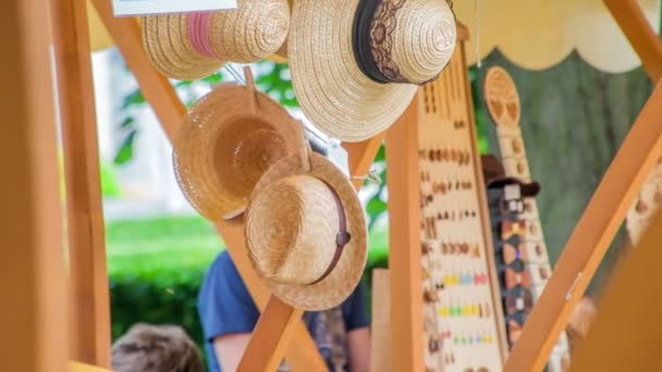 A few beautiful straw hats are hanging down on the stand. People are selling all sorts of items at this festival which is taking place in the summer time.