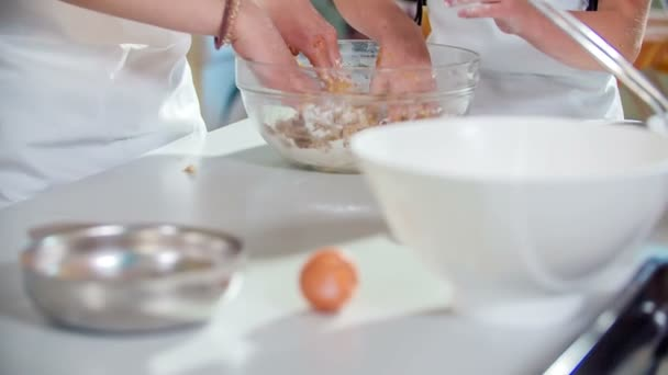Two students are preparing the dough for a chocolate cake in their cooking class. They're kneading the dough.